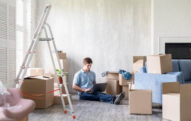 Uomo a casa con scatole e scaletta sempre pronto per uscire