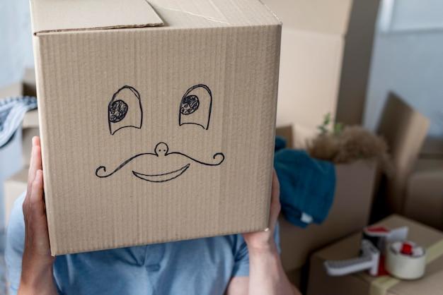 Uomo a casa il giorno del trasloco che agisce sciocco con la scatola sopra la testa