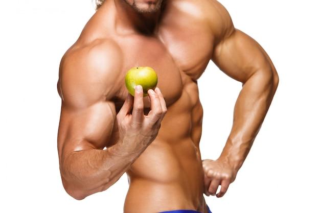 Uomo a forma di e sano del corpo che tiene una frutta fresca della mela, isolata sulla parete bianca