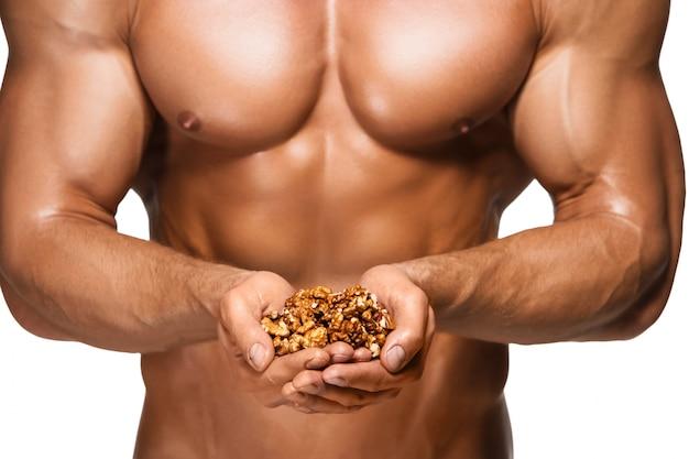 Uomo a forma di ed in buona salute del corpo che tiene le noci, isolate sulla parete bianca