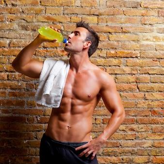 Uomo a forma di muscolo in palestra bevendo rilassato