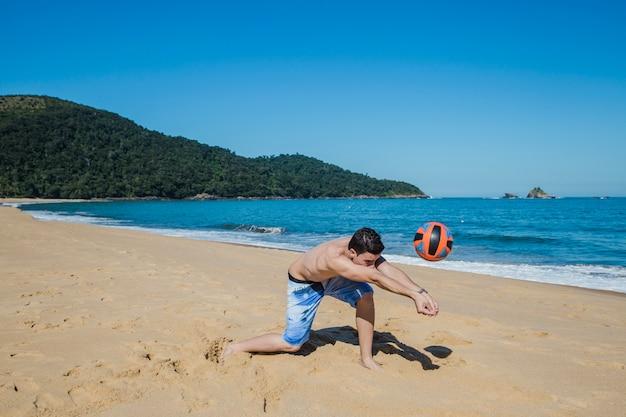 Uomo a giocare a pallavolo sul litorale