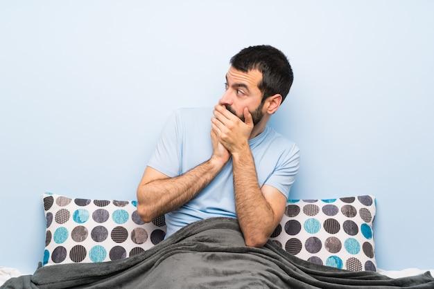 Uomo a letto che copre la bocca e guardando al lato