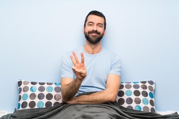 Uomo a letto felice e contando tre con le dita