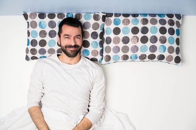 Uomo a letto nella vista dall'alto ridendo