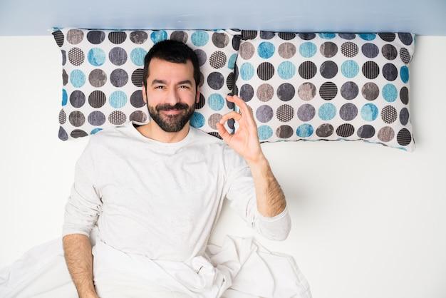 Uomo a letto nella vista superiore che mostra segno giusto con le dita