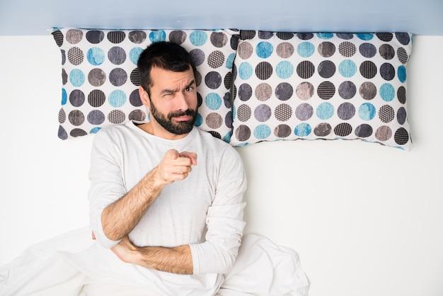 Uomo a letto nella vista superiore frustrato e indicando la parte anteriore