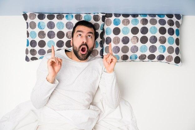 Uomo a letto nella vista superiore sorpreso e rivolto verso l'alto