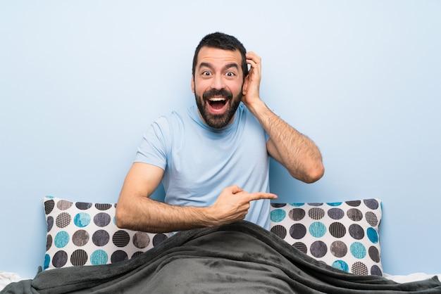 Uomo a letto sorpreso e puntando il dito verso il lato