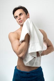 Uomo a medio corpo che asciuga il corpo dopo il bagno