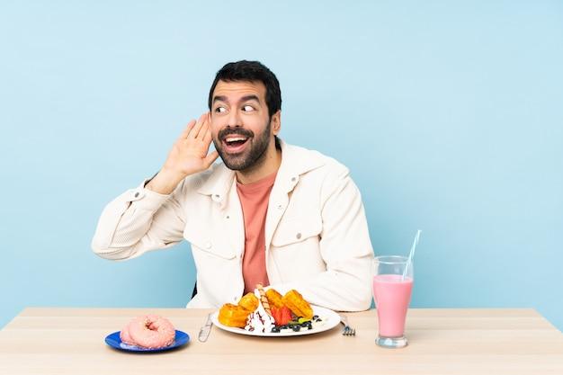 Uomo a un tavolo con cialde per la colazione e un frappè ascoltando qualcosa mettendo la mano sull'orecchio