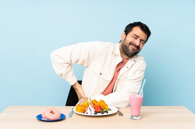 Uomo a un tavolo con cialde per la colazione e un frappè che soffrono di mal di schiena per aver fatto uno sforzo