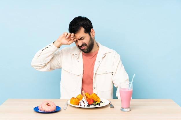 Uomo a un tavolo con cialde per la colazione e un frappè con espressione stanca e malata