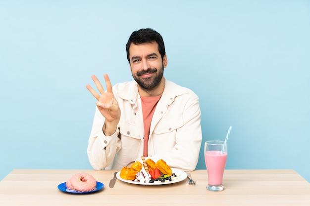 Uomo a un tavolo con cialde per la colazione e un frappè felice e contando tre con le dita
