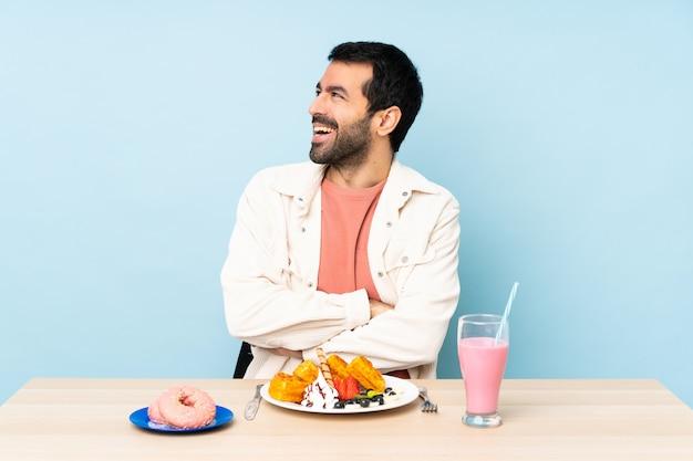 Uomo a un tavolo con cialde per la colazione e un frappè felice e sorridente
