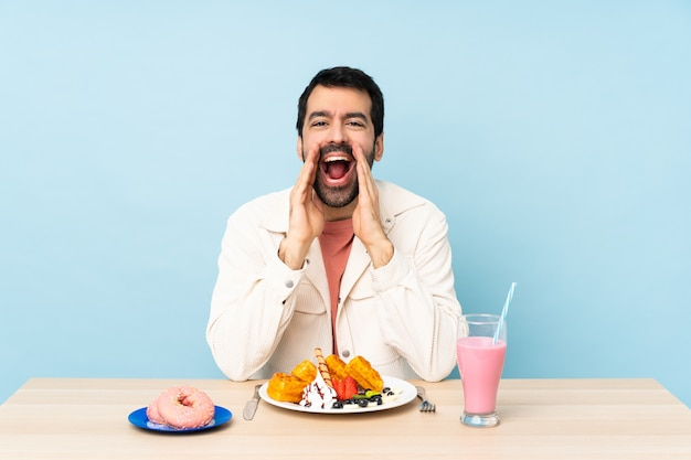 Uomo a un tavolo con cialde per la colazione e un frullato che grida e che annuncia qualcosa