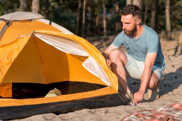 Uomo accovacciato che installa la tenda