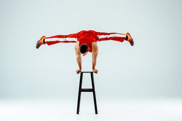Uomo acrobatico su equilibrio posa su uno sgabello
