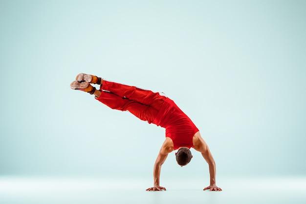 Uomo acrobatico sulla posa dell'equilibrio
