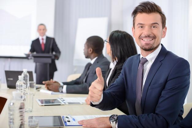 Uomo ad una riunione d'affari che mostra i pollici in su.