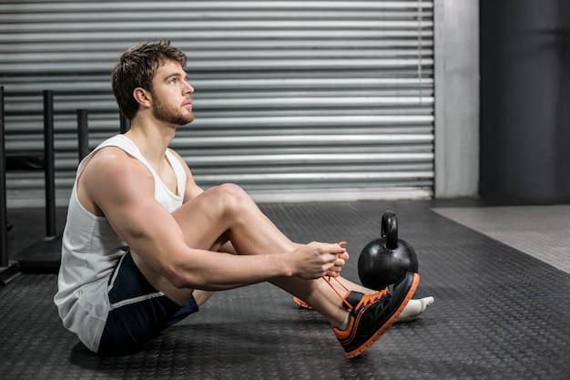 Uomo adatto che lega i suoi lacci della scarpa alla palestra
