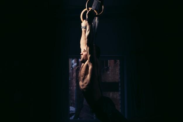 Uomo adatto che tira su sugli anelli relativi alla ginnastica.
