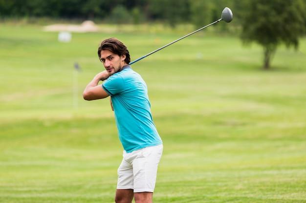 Uomo adatto di vista frontale che gioca golf