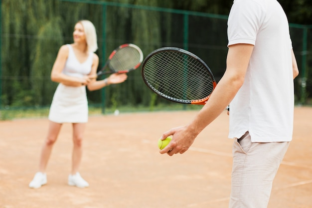 Uomo adatto e donna che esercitano tennis