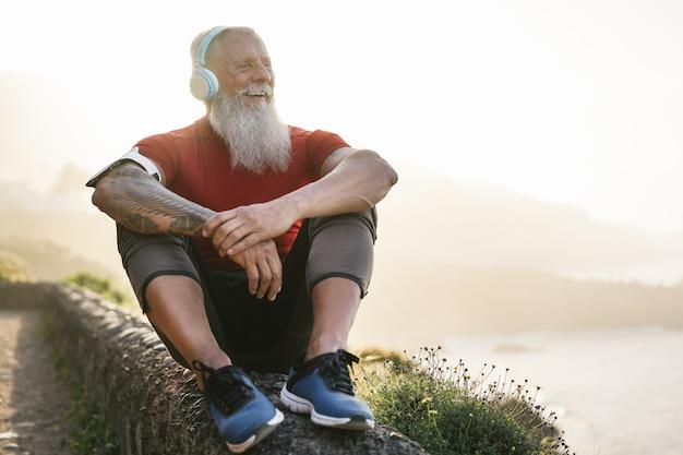 Uomo adatto senior all'aperto al tramonto dopo la sessione di allenamento - addestramento maturo dell'atleta fuori mentre ascoltando la musica della playlist con le cuffie
