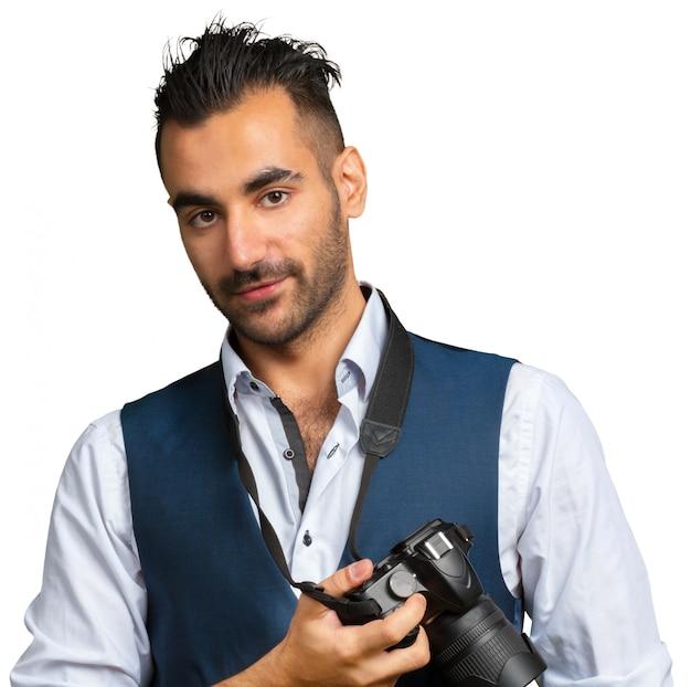 Uomo adulto attraente con una macchina fotografica isolata su bianco