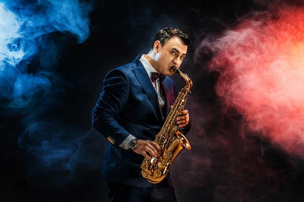 Uomo adulto bello che gioca sassofono