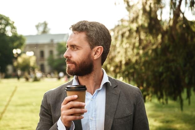 Uomo adulto bello in abito grigio e camicia bianca, guardando da parte mentre beve caffè da asporto durante una passeggiata nel parco verde in una giornata di sole