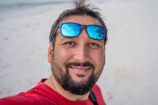 Uomo adulto che prende selfie sulla spiaggia tropicale