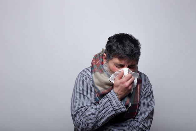 Uomo adulto che soffia il naso da un raffreddore