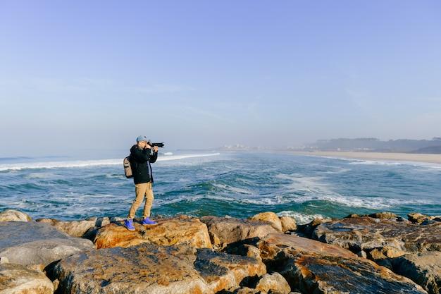 Uomo adulto del viaggiatore che prende una foto di bello paesaggio dal capo dell'oceano