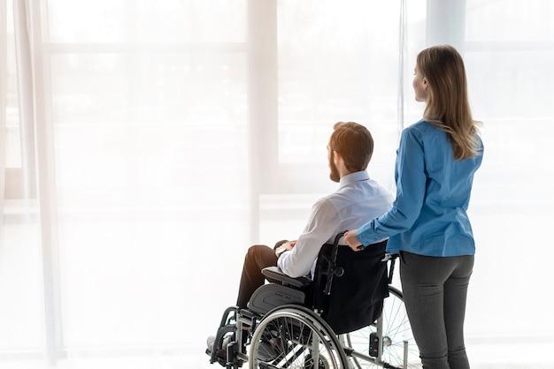 Uomo adulto e donna che esaminano la finestra