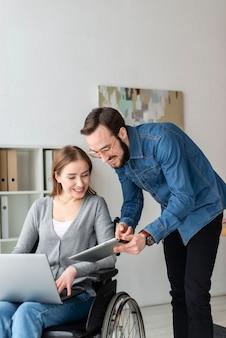 Uomo adulto e donna che lavorano insieme in ufficio