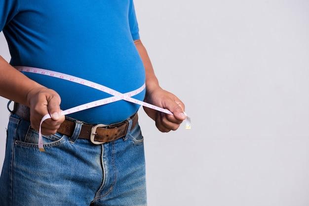 Uomo adulto in sovrappeso o grasso in jeans molto attillati con nastro di misurazione