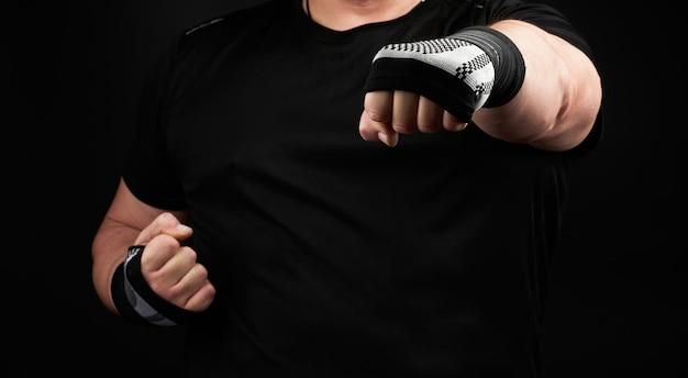 Uomo adulto in uniforme nera e braccia muscolose si trova in una posizione sportiva