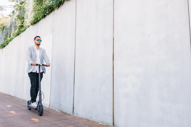 Uomo adulto latino con occhiali da sole, ben vestito ed scooter elettrico sulla strada con uno sfondo cieco bianco