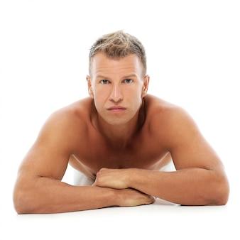 Uomo adulto senza camicia che posa nello studio