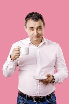 Uomo adulto sorridente con la tazza di caffè che esamina macchina fotografica contro del rosa isolato