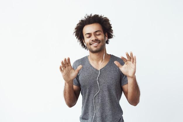 Uomo africano allegro che ascolta la musica in cuffie che ballano cantando.