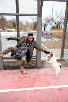 Uomo africano allegro che gioca con il cane e che si diverte all'aperto