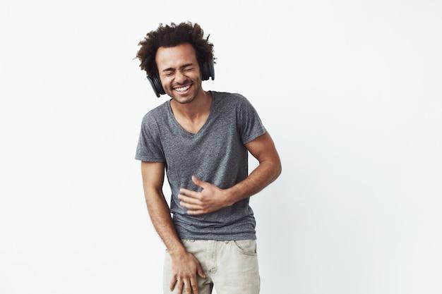 Uomo africano allegro in cuffie che ride occhi chiusi.