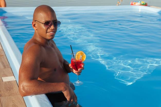 Uomo africano attraente che gode del suo drink alla piscina, spazio della copia. uomo felice che si rilassa nello stagno durante le sue vacanze estive
