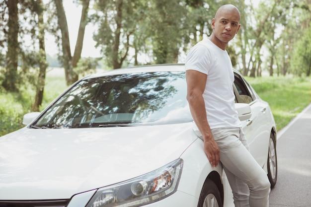 Uomo africano bello che gode del viaggio in macchina su un roadtrip