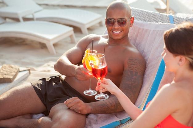 Uomo africano bello con i vetri tintinnanti atletici del corpo muscoloso con la sua ragazza, celebrante anniversario al centro balneare. coppia di innamorati che viaggiano insieme in estate