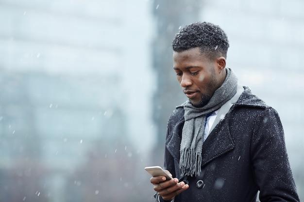 Uomo africano bello con lo smartphone in neve