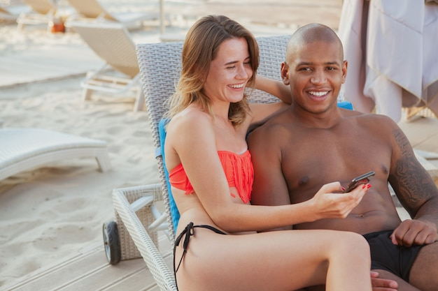 Uomo africano bello felice che ride, godendo di mentire sulla spiaggia con la sua bella fidanzata, copia spazio. giovani coppie multietniche che godono viaggiando insieme alla spiaggia